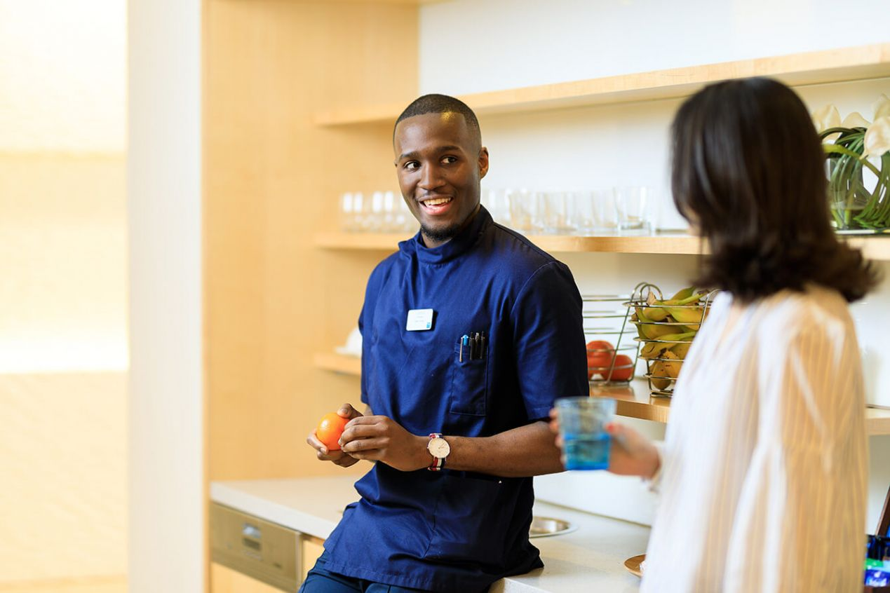 Black-male-nurse-talking-to-woman-in-kitchen-area-of-Bupa-centre.jpg